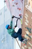 Man climbs upward on ice climbing competition Stock Photos