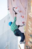 Man climbs upward on ice climbing competition Royalty Free Stock Image