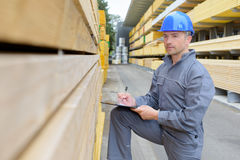 Man with clipboard assessing stack wood. Man with clipboard assessing stack of wood Royalty Free Stock Photos