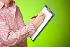 Man with clipboard. Man holding a clipboard and taking a notes with pen Royalty Free Stock Photo
