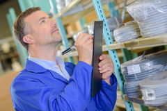 Man with clipboard next to shelf electric cable Stock Photo