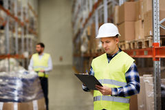 Man with clipboard in safety vest at warehouse Stock Photo