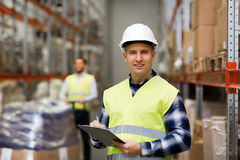 Man with clipboard in safety vest at warehouse. Wholesale, logistic, people and export concept - men with clipboard in reflective safety vest at warehouse Stock Images