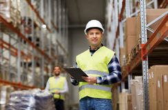 Man with clipboard in safety vest at warehouse. Wholesale, logistic, people and export concept - men with clipboard in reflective safety vest at warehouse stock photography