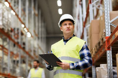 Man with clipboard in safety vest at warehouse. Wholesale, logistic, people and export concept - men with clipboard in reflective safety vest at warehouse stock image