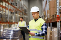 Man with clipboard in safety vest at warehouse. Wholesale, logistic, people and export concept - men with clipboard in reflective safety vest at warehouse Stock Photos