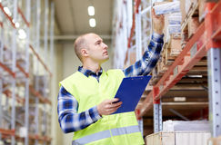 Man with clipboard in safety vest at warehouse. Wholesale, logistic, people and export concept - man with clipboard in reflective safety vest at warehouse stock image