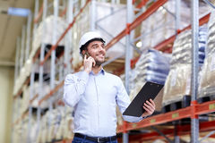 Man with clipboard and smartphone at warehouse Stock Photography