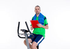 Man with clipboard train on fitness machine Royalty Free Stock Photography