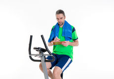 Man with clipboard train on fitness machine Royalty Free Stock Image