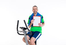Man with clipboard train on fitness machine Stock Images