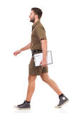 Man with clipboard walking. Happy man in khaki uniform walking and carrying clipboard. Full length studio shot isolated on white Royalty Free Stock Photos