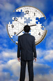 Man and clock. Man in suit standing in front of a clock puzzle with missing pieces Stock Images