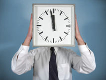 Man with clock. A man holds up a huge clock, covering his face. He's dressed in a shirt and tie, with the clock showing a time that is close to 12 o'clock stock image