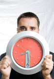 Man with clock. A young man holding a clock in front of his face, looking a little bit scared and worried royalty free stock photos
