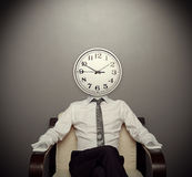 Man with a clock instead of a head. Sitting on chair Stock Images