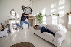 Man-clock jumping near a girl who lies on the couch in the loft. The man with a big clock instead of his head. Time concept Royalty Free Stock Photo