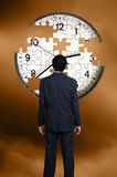 Man and clock puzzle. Man in suit standing in front of a clock puzzle with missing pieces Stock Image
