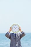 Man with clock on seaside Stock Photography