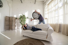 Man-clock waking the girl who lies on the couch in the loft. The man with a big clock instead of his head. Time concept Stock Photography