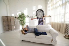Man-clock waking the girl who lies on the couch in the loft. The man with a big clock instead of his head. Time concept Royalty Free Stock Photo