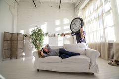 Man-clock waking the girl who lies on the couch in the loft. The man with a big clock instead of his head. Time concept Royalty Free Stock Photos