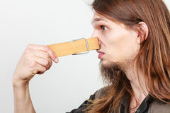 Man with clogged nose by clothespin. Unpleasant bad smell concept. Portrait of young long haired man with clogged nose by big clothespin Royalty Free Stock Photos