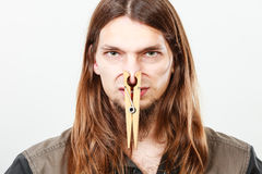 Man with clogged nose by clothespin. Unpleasant bad smell concept. Portrait of young long haired man with clogged nose by big clothespin Royalty Free Stock Photography