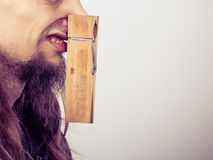 Man with clogged nose by clothespin. Unpleasant bad smell concept. Portrait of young long haired man with clogged nose by big clothespin Stock Image