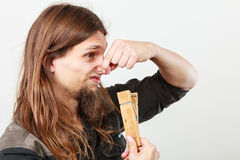 Man with clogged nose by clothespin. Unpleasant bad smell concept. Portrait of young long haired man with clogged nose by big clothespin Stock Photos