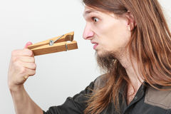Man with clogged nose by clothespin. Unpleasant bad smell concept. Portrait of young long haired man with clogged nose by big clothespin stock photography