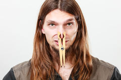 Man with clogged nose by clothespin. Unpleasant bad smell concept. Portrait of young long haired man with clogged nose by big clothespin Royalty Free Stock Image
