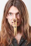 Man with clogged nose by clothespin. Unpleasant bad smell concept. Portrait of young long haired man with clogged nose by big clothespin Royalty Free Stock Images