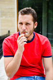 Man. Close up Portrait of Young attractive angry  bearded man smoking outdoor Stock Photo