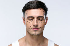 Man with closed eyes. And marked with lines for plastic surgery Royalty Free Stock Photo