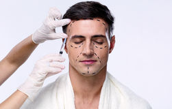 Man with closed eyes. At plastic surgery with syringe in his face Royalty Free Stock Photos