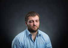 Man with closed eyes. Man wearing blue shirt dreaming with closed eyes over black Royalty Free Stock Photo