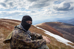 Man with closed face and camouflage clothing sitting on mountain Royalty Free Stock Image