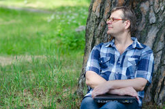 Man with closed laptop is resting in pine forest. Near large trunk of old pine Royalty Free Stock Photo