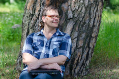 Man with closed laptop is resting in pine forest. Near large trunk of old pine tree Stock Image