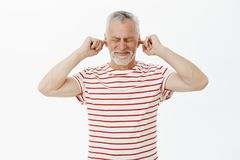 Man closes ears and eyes with intense irritated expression hearing loud disturbing sound waiting till noise disappear. Standing bothered and annoyed against stock images