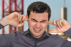 Man closes ears with fingers to protect from loud noise Stock Photos