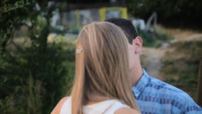 Man closes girl's eyes with his hands for surprise. HD stock footage