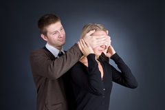 The man closes hands behind an eye of the girl. Royalty Free Stock Photos
