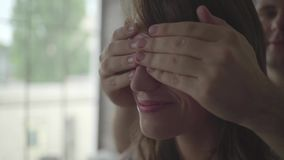 Man closes his is girlfriend`s eyes stock video footage