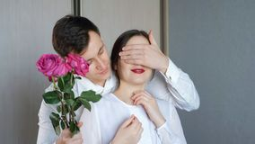 Man closes his is girlfriend`s eyes to make surprise and gives roses stock photos