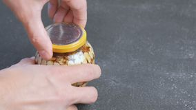 Man closes the lid of a jar of nuts in honey. Hands close-up. Man closes the lid of a jar of nuts in honey stock video