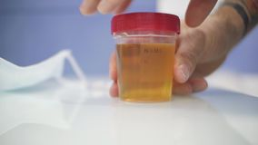 A man closes the lid of the urine container with analyzes.container for urine analysis.  stock video footage