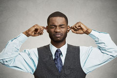 Man Closing Ears Avoiding Unpleasant Conversation, Situation. Closeup portrait unhappy, annoyed man plugging closing ears with fingers, disgusted ignoring Royalty Free Stock Images