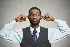 Man Closing Ears Avoiding Unpleasant Conversation, Situation. Closeup portrait unhappy, annoyed man plugging closing ears with fingers, disgusted ignoring Royalty Free Stock Image